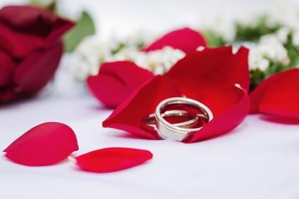 Eheringe in roten Rosenblättern